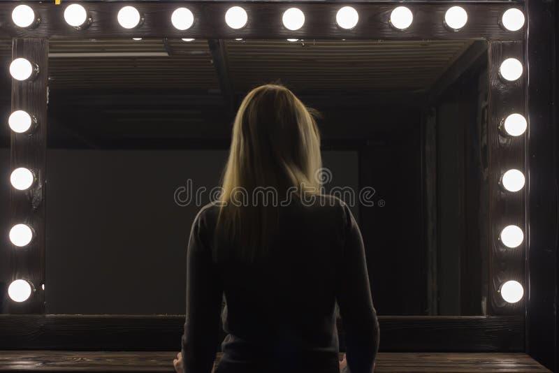 Partijmeisje die zich voor een spiegel bevinden, stock foto