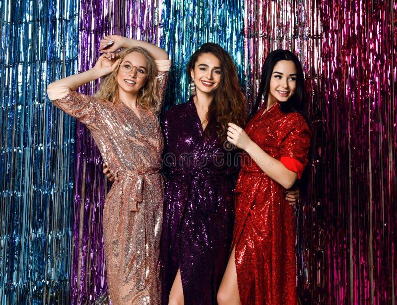 Partijtijd van drie mooie modieuze vrouwen die in elegante uitrusting nieuw jaar, verjaardag vieren, die pret, het dansen hebben stock foto