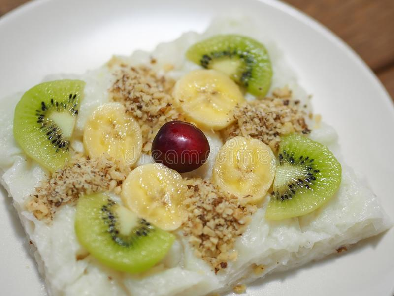 Partikel Türkisch-spezifischer rosafarbener Pudding gullac Bonbon und der Bananenkiwi und -walnuß stockbild