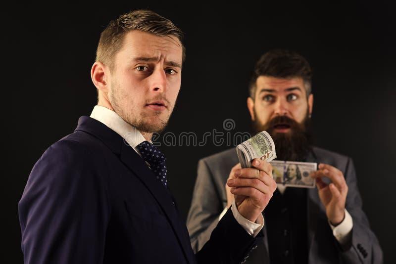 Partilha do conceito dos lucros Reunião de homens de negócios respeitáveis, fundo preto Homem no rolo sério da posse da cara feit foto de stock