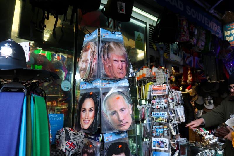 Partimaskeringar av trumf, den Putin prinsen Harry och Meghan Markle på försäljning tillsammans med vykort i conviencelager i Lon royaltyfria foton