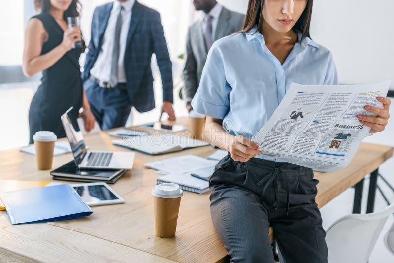 partisk sikt av affärskvinnaläsningtidningen och kollegor bakom arkivfoton