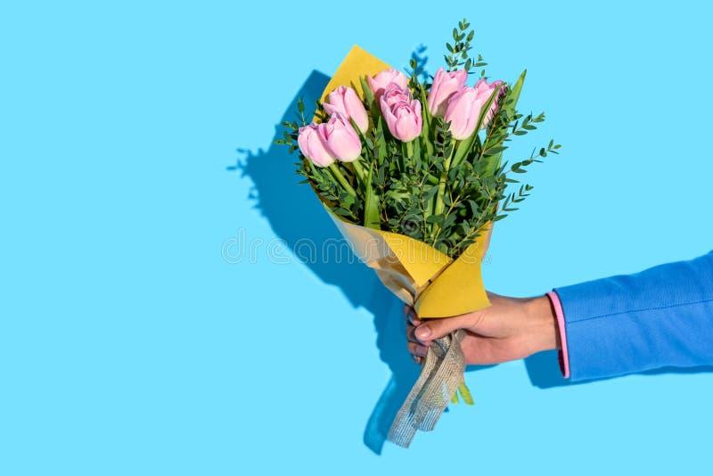 partisk sikt av den hållande buketten för afrikansk amerikanman av blommor på blå bakgrund arkivbilder