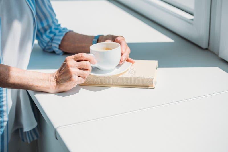partisk sikt av den höga kvinnan med boken och koppen kaffe på fönsterbräda hemma arkivfoton