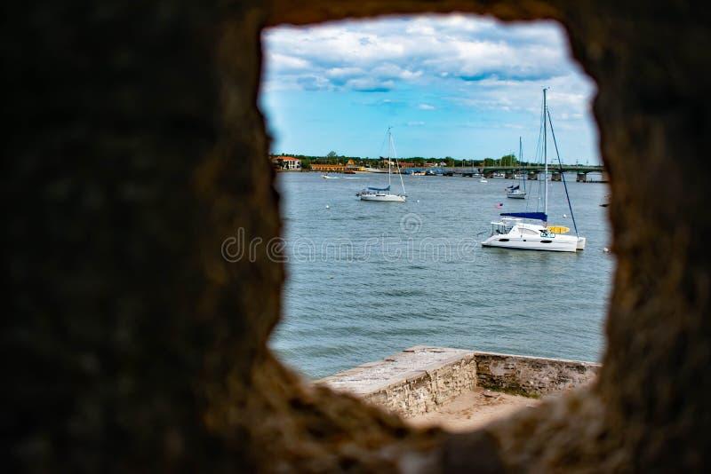 Partisk sikt av den Matanzas floden och segelbåtar från stentornfönster i Castillo de San Marcos Fort på Florida historiska kust royaltyfri bild