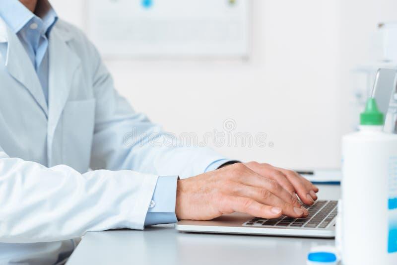 partisk sikt av doktorn i det vita laget som arbetar på bärbara datorn på arbetsplatsen royaltyfria bilder