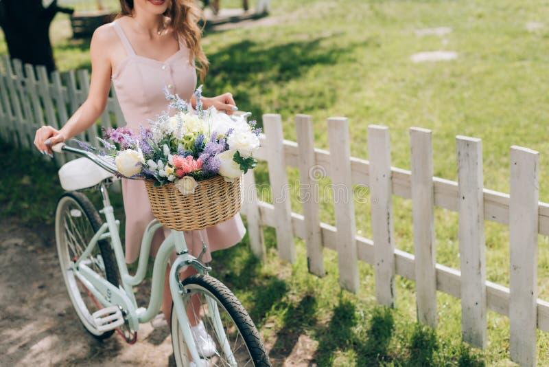 partisk sikt av kvinnan i stilfull klänning med den retro cykeln med den vide- korgen som är full av blommor arkivfoton