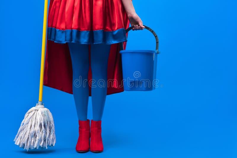 partisk sikt av kvinnan i superherodräkt med golvmopp och hinken för att göra ren royaltyfria bilder