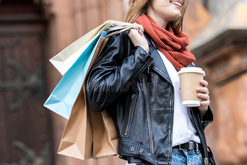 partisk sikt av kvinnan med shoppingpåsar och kaffe som går arkivbild