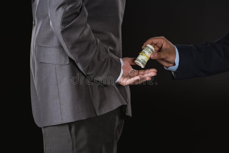 Partisk sikt för närbild av affärsmannen som ger pengar och muter affärspartnern royaltyfri bild