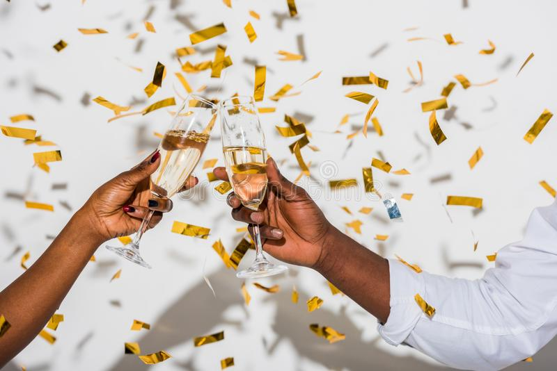 partisk sikt för närbild av afrikansk amerikanpar som klirrar exponeringsglas av champagne på vit arkivfoton