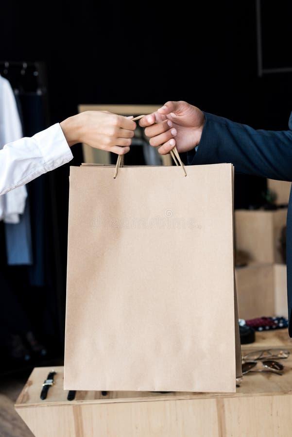 partisk sikt för närbild av säljaren som ger shoppingpåsar till affärsmannen royaltyfri fotografi