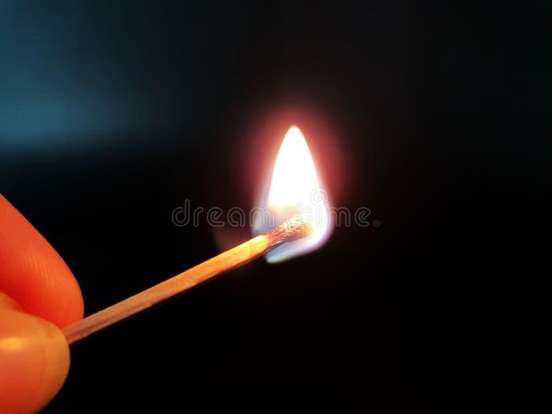 Partita bruciante a disposizione su fondo neutrale immagini stock libere da diritti