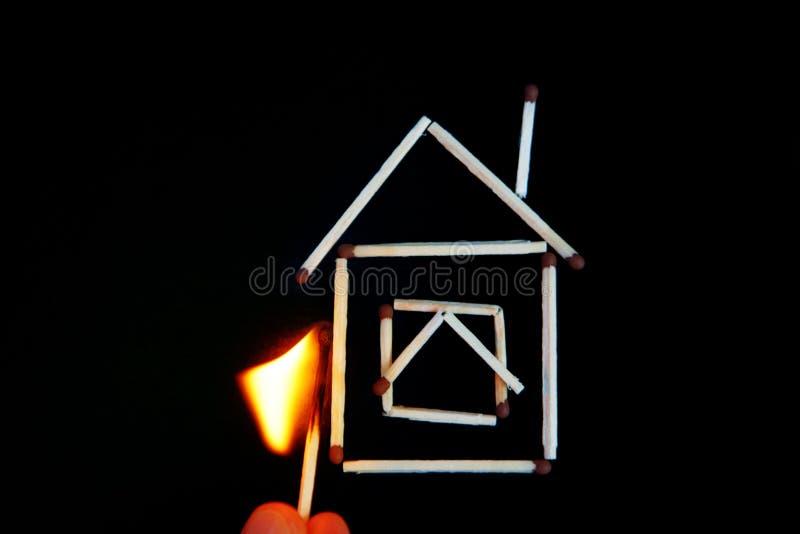 partita bruciante vicino al modello di una casa immagine stock