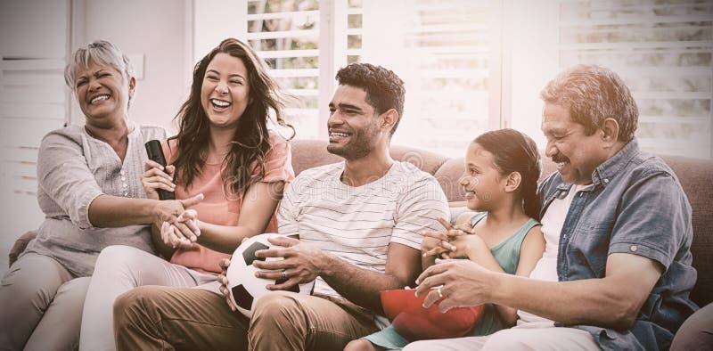 Partita di calcio di sorveglianza della famiglia di diverse generazioni felice sulla televisione in salone immagini stock