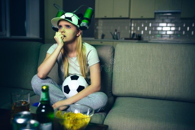 Partita di football americano dell'orologio della giovane donna sulla TV alla notte Il modello biondo infelice di ribaltamento si immagini stock