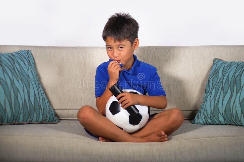 Partita di football americano di sorveglianza felice ed emozionante del giovane ragazzo ispanico sullo strato del salone della te fotografie stock libere da diritti