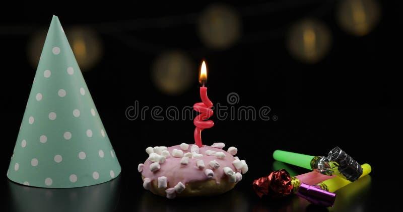 Partito Ciambella rosa e una candela festiva rossa su  immagine stock libera da diritti