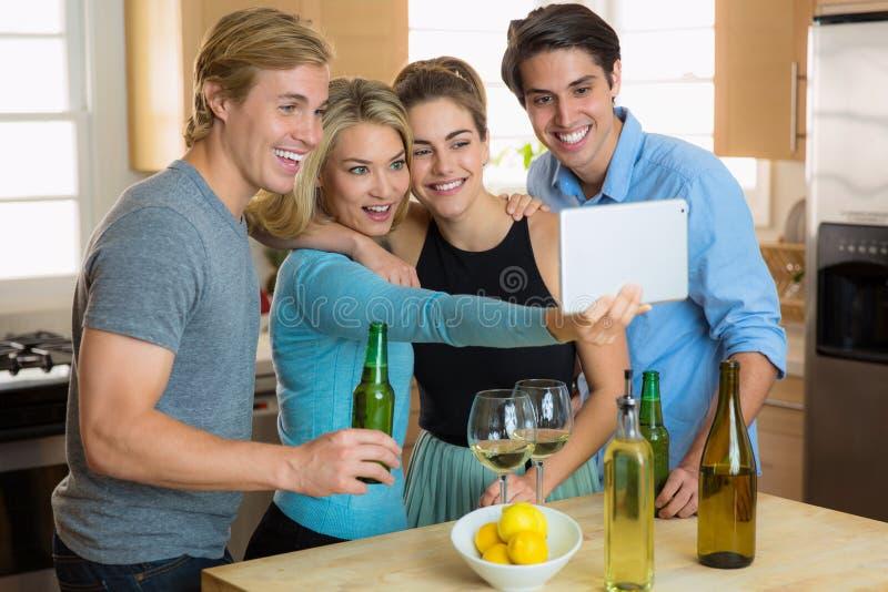 Partito del selfie della riunione della famiglia sulle coppie di una compressa due ad un appuntamento a quattro fotografia stock libera da diritti