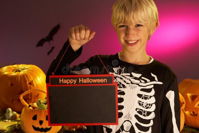 Partito di Halloween con un segno della holding del bambino del ragazzo fotografia stock libera da diritti
