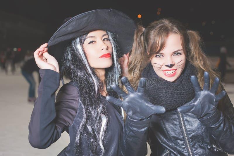 Partito di Halloween! Le giovani donne gradiscono il ruolo del gatto e della strega fotografie stock