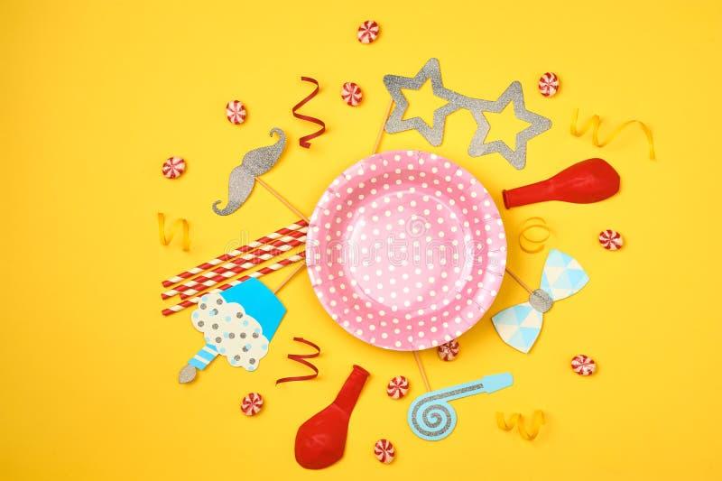 Partito, dolci e coriandoli colorati sul modello giallo di vista superiore del fondo fotografia stock libera da diritti