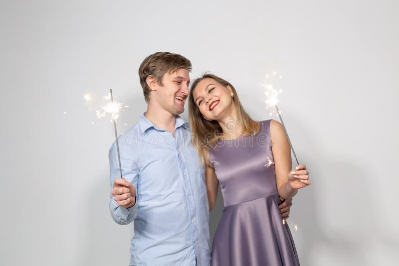 Partito, famiglia e concetto di feste - giovane coppia che tiene le stelle filante su fondo bianco immagini stock