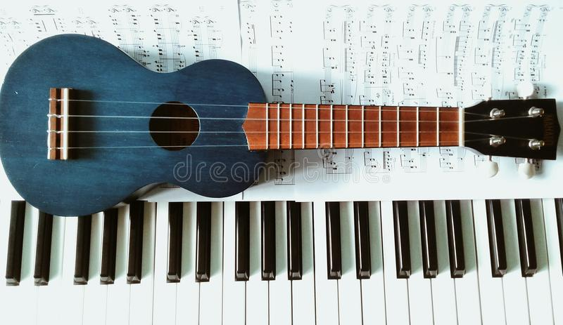Partituras Ukulele y un piano. Ukulele and a piano Sheet music. Un Ukulele azul sobre unas partituras y un piano. A blue Ukulele on some sheet music and a piano royalty free stock images