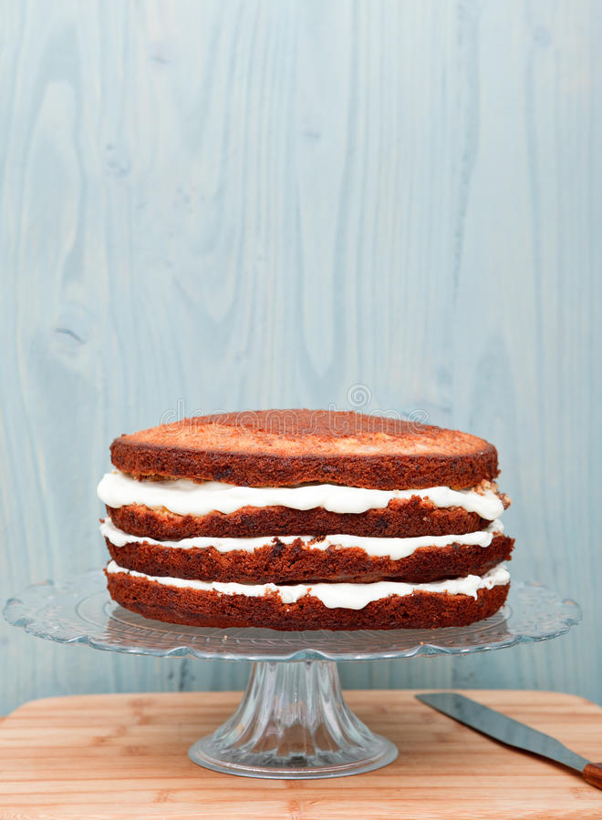 Partly frosted cake on a glass stand, decoration in a process. Blue wall background royalty free stock image
