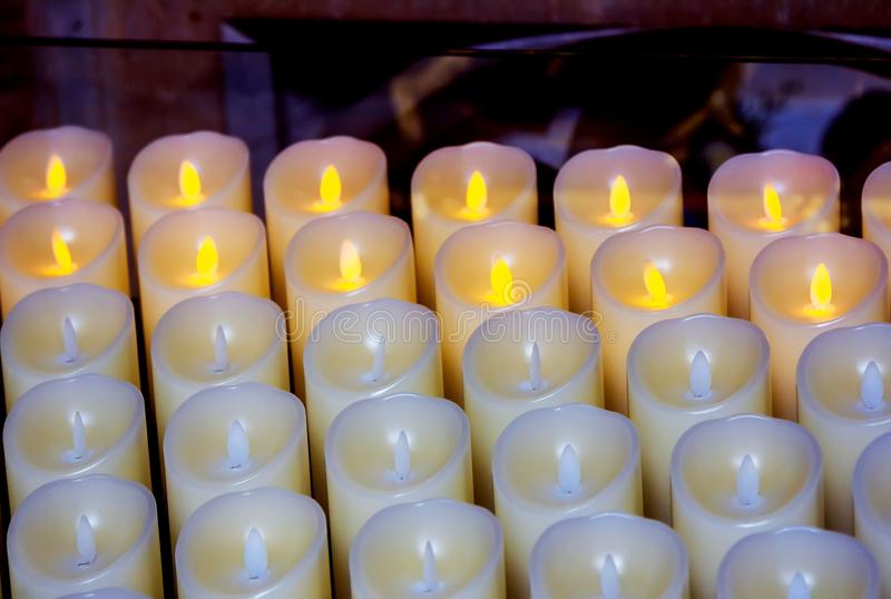 Partly lighted modern plastic candles in a church. Indoors fire preventing electric equipment stock photography