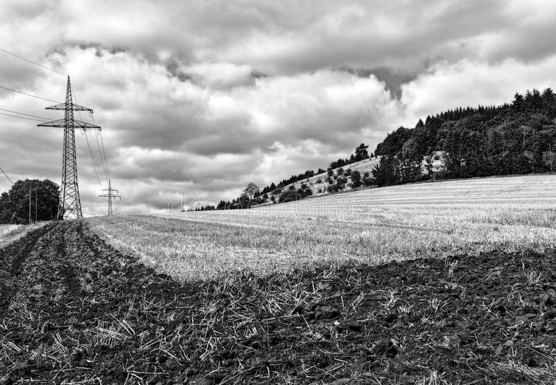 Partly ploughed field after the harvest with transmission tower and wooded hill in the background royalty free stock photos