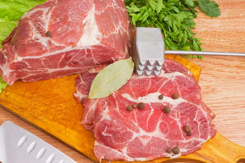 Partly sliced pork neck on cutting board, spices, meat tenderize royalty free stock photos