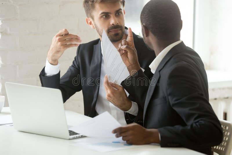 Partner africani e caucasici multirazziali che discutono a stante in disaccordo fotografia stock