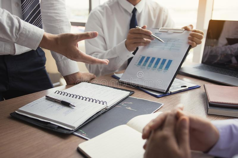 Partner colleagues are talking about the results in the document on hand and together analyze the work data about the company`s. Financial statements stock photography