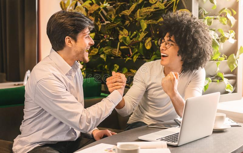 Partner emozionanti che celebrano successo del loro progetto di piccola impresa immagini stock