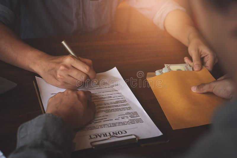 Partner give bribe money in envelope to another businessman and pointing at sign permit contract. Corruption and Anti Bribery royalty free stock photography