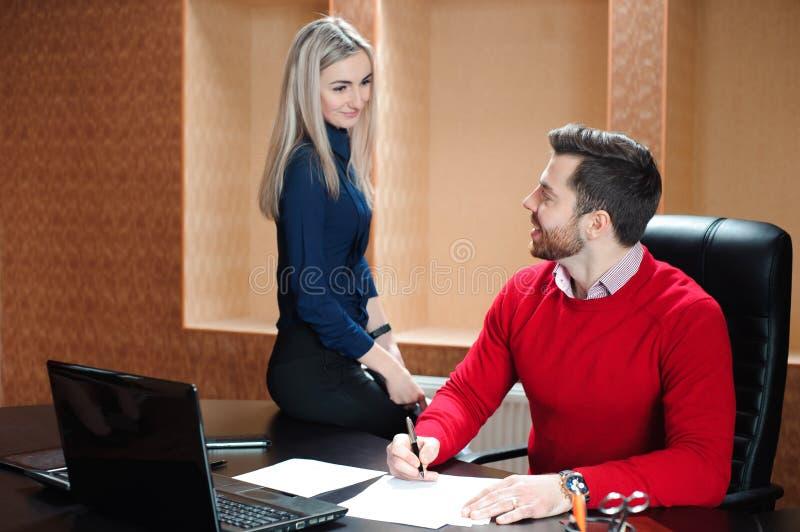 Partnera biznesowego obsiadanie przy stołem przed obliczającym fotografia stock