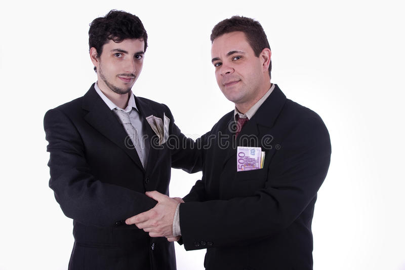 Partners. Portrait of businessmen shaking hands, with dollar and euro currency on their pocket, suggesting commerce between partners royalty free stock image