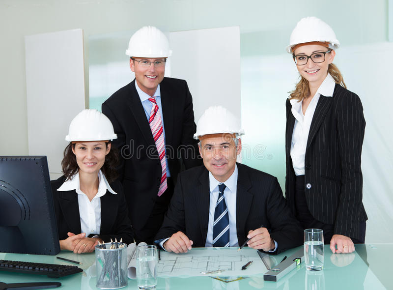 Partners in an architectural firm. Four diverse professional partners in an architectural firm posing behind a table in an office wearing their hardhats and royalty free stock photos