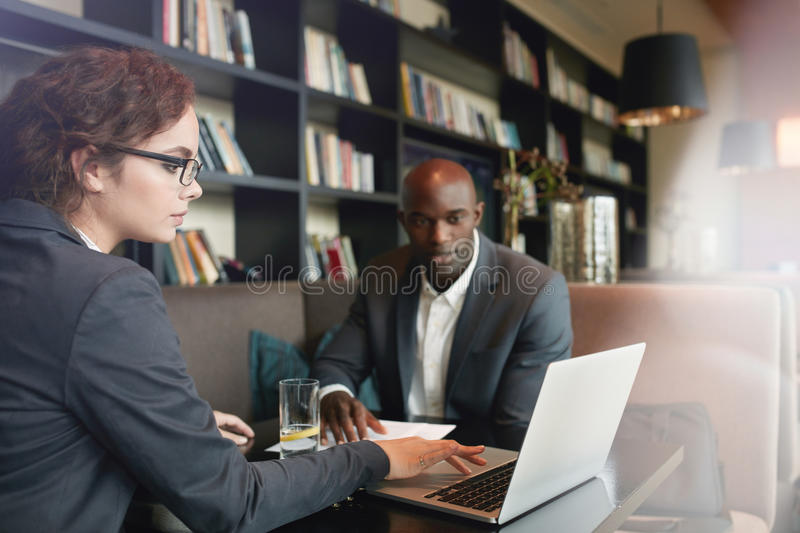 Partners at coffee shop meeting for new business discussions. Young businesswoman working on laptop with her business partner while sitting at cafe. Young stock photography
