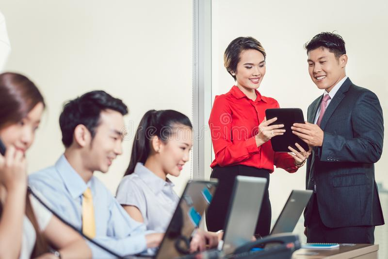 Partners die bespreking hebben die digitale tablet gebruiken stock foto's