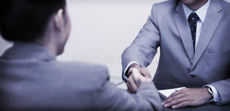 Partners die bij lijst het schudden handen zitten royalty-vrije stock foto