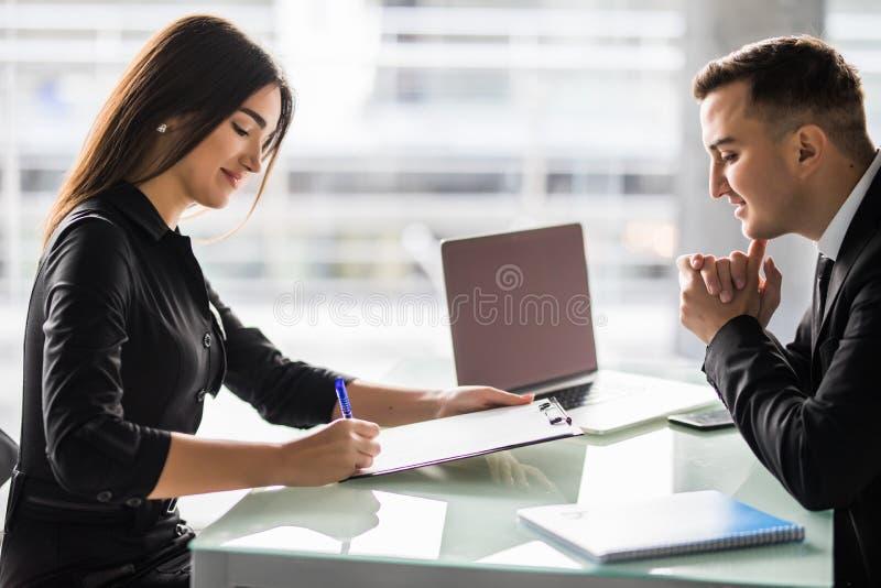 Partners die contract ondertekenen bij bureau Het contract van het vrouwenteken in bureau royalty-vrije stock afbeelding