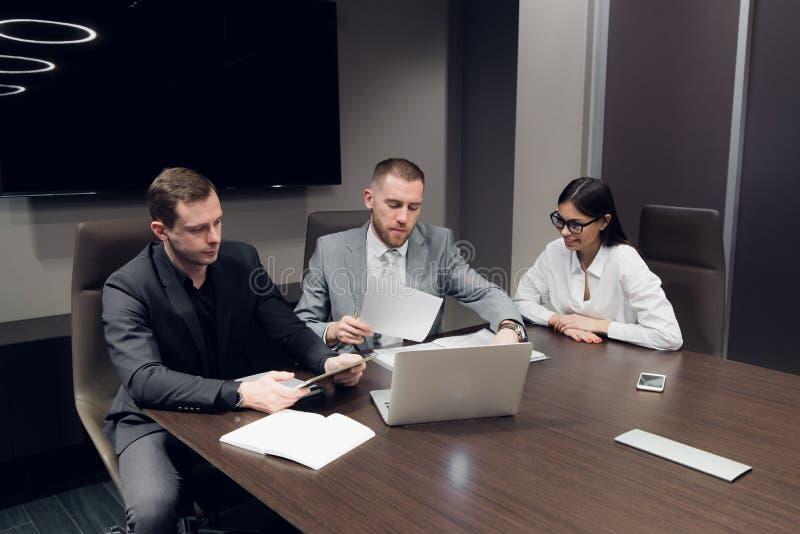 Partners die documenten en ideeën bespreken op vergadering stock afbeeldingen