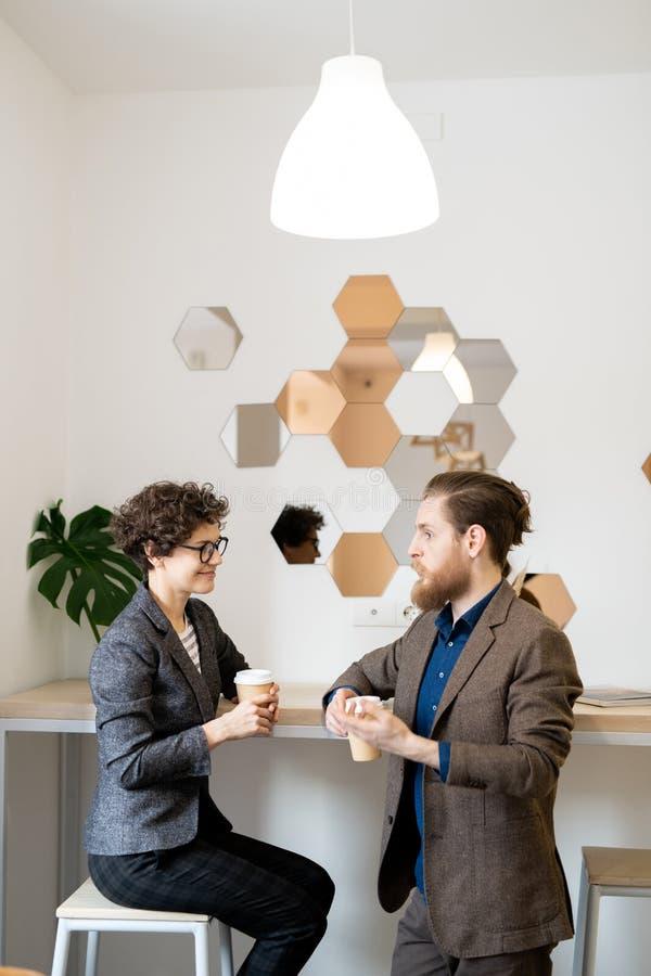 Partners die projectontwikkeling in koffie bespreken stock afbeeldingen