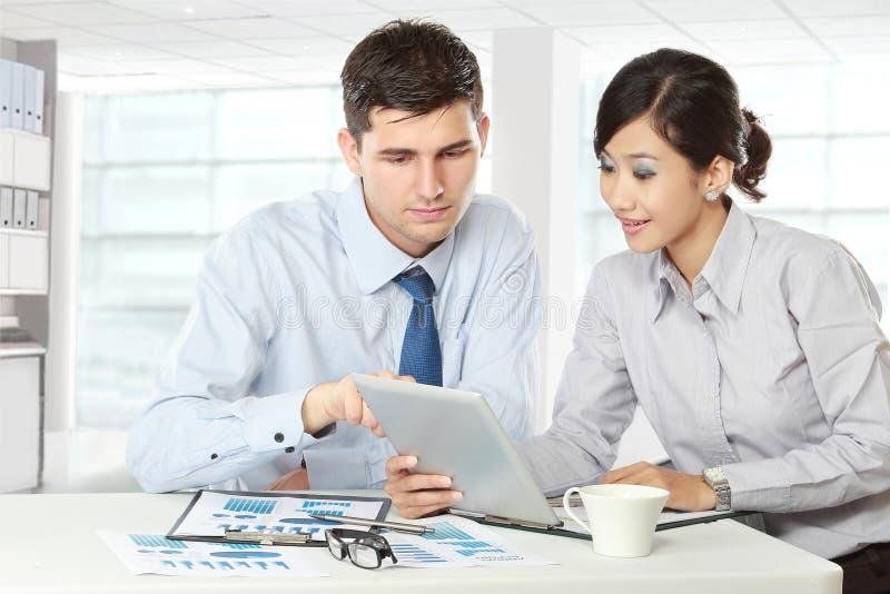 Partners die touchpad op vergadering gebruiken royalty-vrije stock afbeeldingen