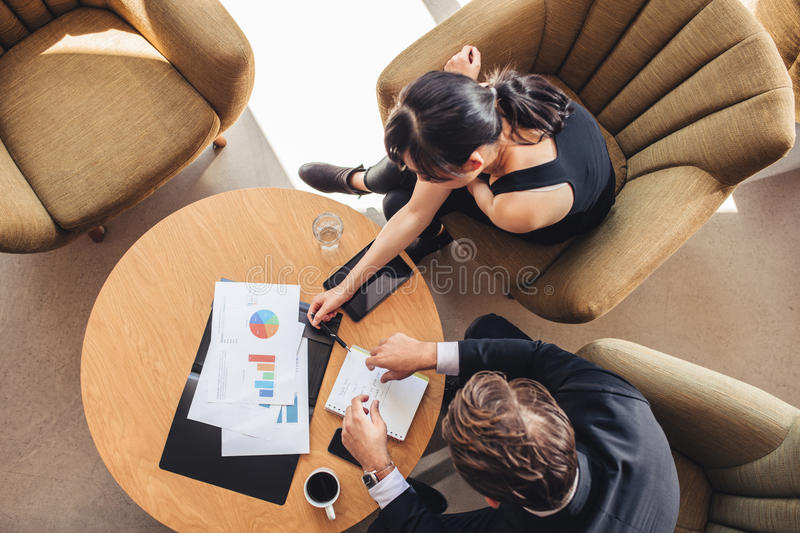 Partners discussing new project in office lobby royalty free stock images