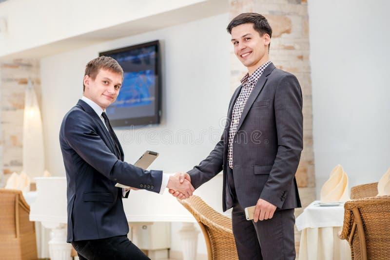 Partners het samenkomen! Jonge zakenman twee die bevinden zich tegenover royalty-vrije stock afbeelding