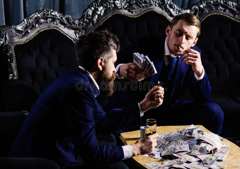 Partners met de zeker dollars van de gezichtengreep en champagneglas Uitstekend duur meubilair, premie, contant geld royalty-vrije stock foto