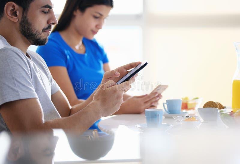 Partners som använder telefonen, medan äta frukosten tillsammans arkivfoto